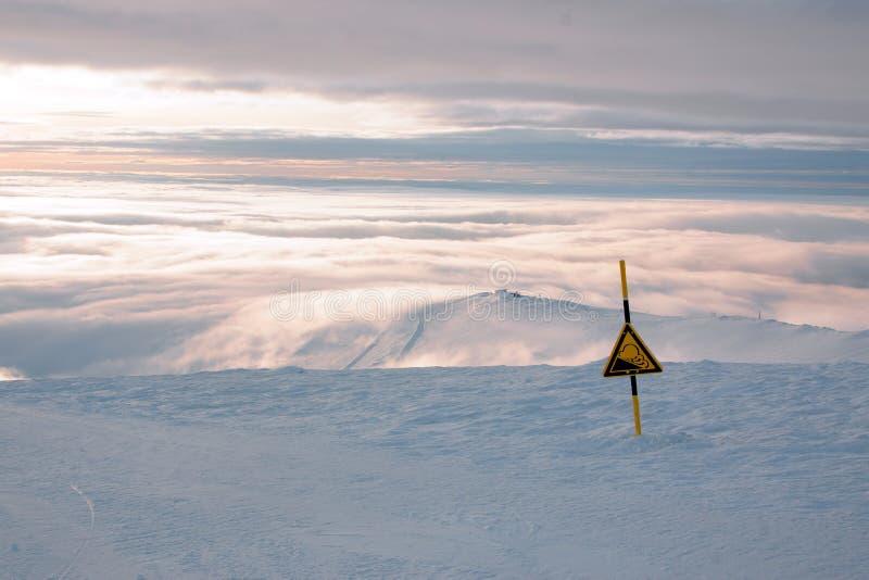 Ένα σημάδι του κινδύνου ή της απότομης καθόδου στη διαδρομή σε ένα χιονοδρομικό κέντρο το χειμώνα, ένα τοπίο με το χιόνι και τα σ στοκ φωτογραφία