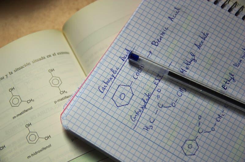 Ένα σημειωματάριο και ένα βιβλίο με τους τύπους της οργανικής χημείας στοκ φωτογραφίες