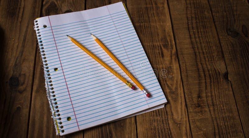 Ένα σημειωματάριο με τα μολύβια στο ξύλινο υπόβαθρο στοκ φωτογραφίες με δικαίωμα ελεύθερης χρήσης