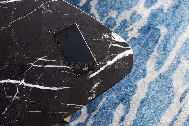 Ένα σκαμνί φιαγμένο από τεχνητή πέτρα στέκεται σε έναν τάπητα με το λεπτό NAP, μια τοπ άποψη Το κινητό τηλέφωνο βρίσκεται σε ένα  στοκ εικόνες
