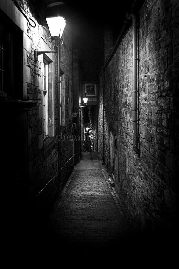 Ένα σκοτεινό, στενό ευρωπαϊκό δρομάκι τη νύχτα, περικυκλωμένο από τούβλα και πετράδι Φωτισμός μόνο με ορισμένες λυχνίες στοκ φωτογραφίες