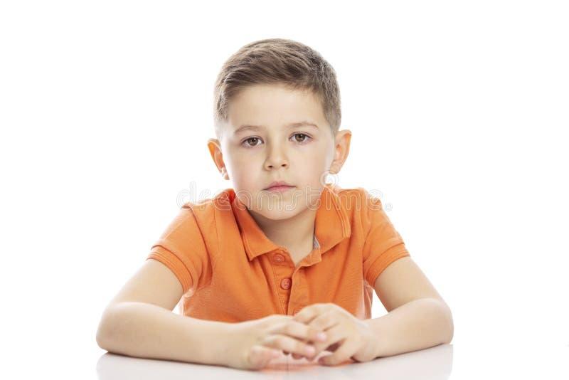 Ένα σοβαρό σχολικής ηλικίας αγόρι σε μια φωτεινή πορτοκαλιά μπλούζα πόλο κάθεται στον πίνακα E Isolirvoan σε ένα άσπρο υπόβαθρο στοκ εικόνα με δικαίωμα ελεύθερης χρήσης