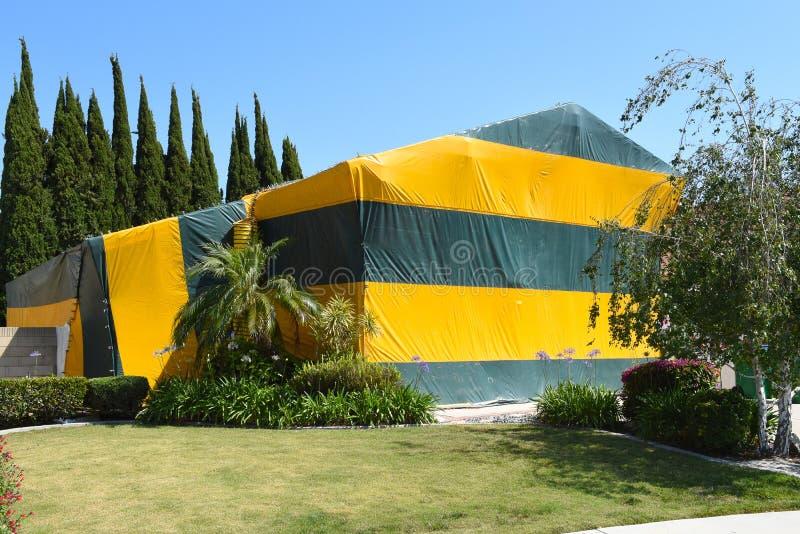 Ένα σπίτι δύο ιστορίας σκεπασμένο με τέντα για τον υποκαπνισμό, μια μέθοδος ελέγχου παρασίτων για τους τερμίτες, η οποία γεμίζει  στοκ φωτογραφία