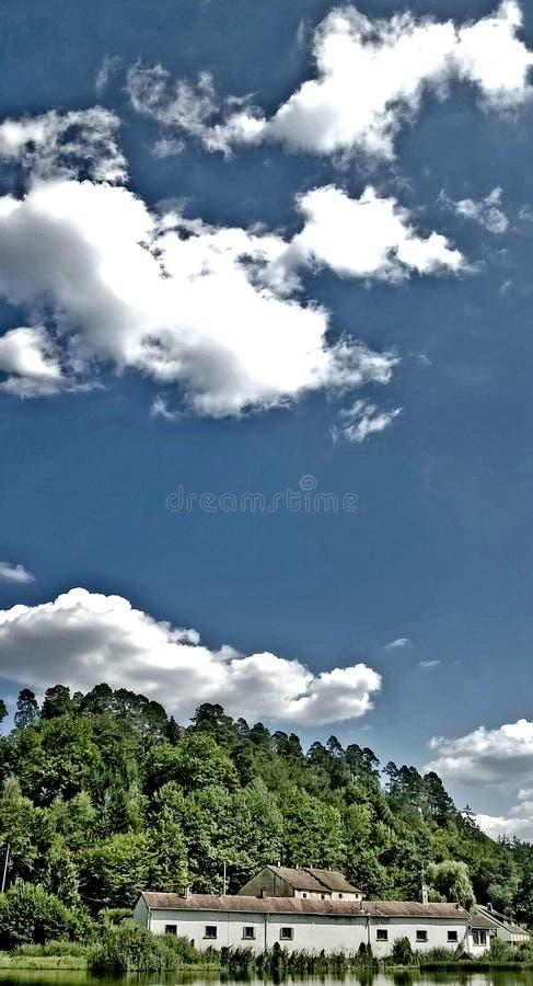 Ένα σπίτι στη λίμνη με το μπλε ουρανό και τα άσπρα σύννεφα στοκ εικόνες