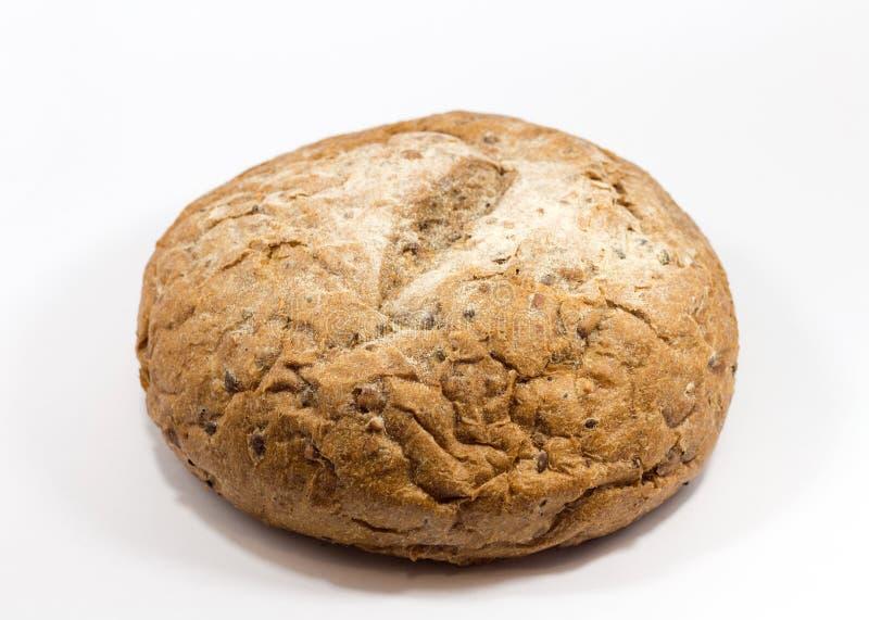 Ένα στρογγυλό ψωμί σιταριού που απομονώνεται σε ένα άσπρο υπόβαθρο Ολόκληρο φρέσκο μικρό ψωμί σίτου και σίκαλης με πολλούς σπόρου στοκ εικόνα
