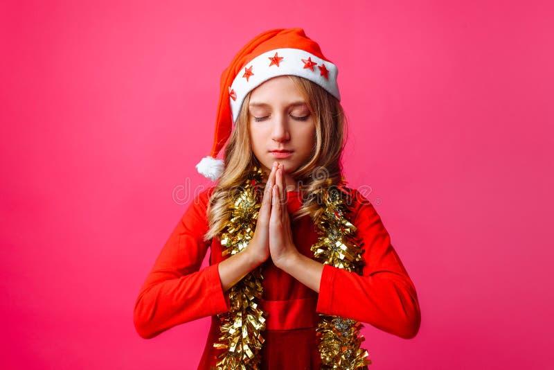 Ένα συγκεντρωμένο κορίτσι, μια μαθήτρια σε ένα καπέλο Santa και με tinsel στοκ εικόνα