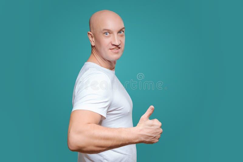 Ένα συναισθηματικό άτομο σε μια άσπρη μπλούζα παρουσιάζει με μια χειρονομία χεριών ότι όλα έχουν δροσιά, σε ένα υπόβαθρο Titian στοκ φωτογραφία