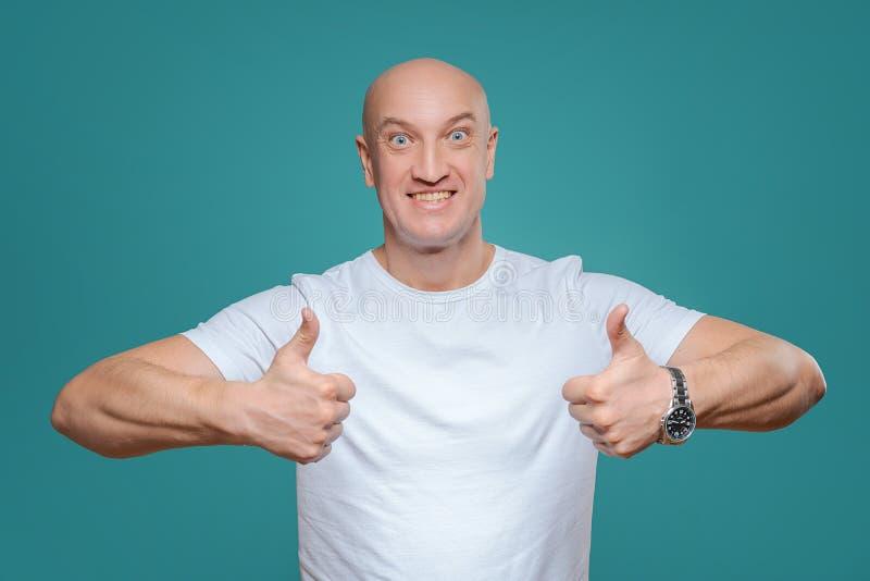 Ένα συναισθηματικό άτομο σε μια άσπρη μπλούζα παρουσιάζει με μια χειρονομία χεριών ότι όλα έχουν δροσιά, σε ένα υπόβαθρο Titian στοκ φωτογραφία με δικαίωμα ελεύθερης χρήσης