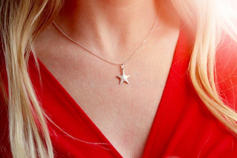 Ένα σχίσιμο γυναικών ` s με ένα αστέρι διαμόρφωσε το περιδέραιο στοκ φωτογραφία