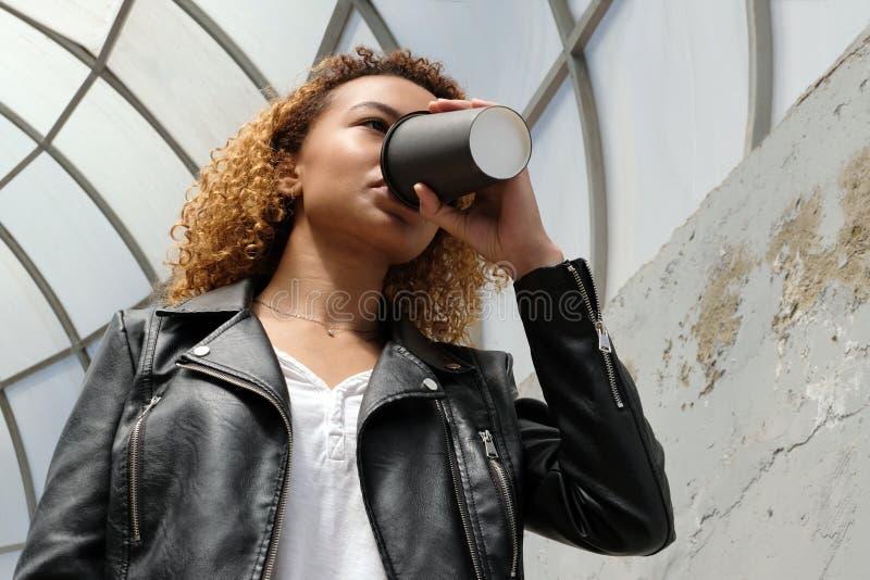 Ένα σύγχρονο νέο κορίτσι αφροαμερικάνων σε ένα σακάκι δέρματος πίνει τον καφέ ή ένα άλλο ποτό από ένα μαύρο ποτήρι στην οδό Lif στοκ εικόνες