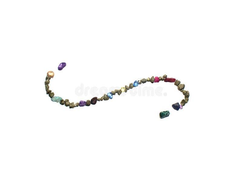 Ένα σύμβολο στροβίλου διαιρετών σελίδων έκανε από τους χρυσούς, μπλε και κόκκινους λαμπρούς βράχους και τους πολύτιμους λίθους στοκ εικόνες