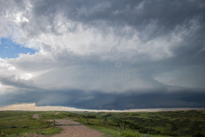 Ένα σύννεφο θύελλας supercell κρεμά χαμηλά στον ουρανό πέρα από το λιβάδι στοκ εικόνες