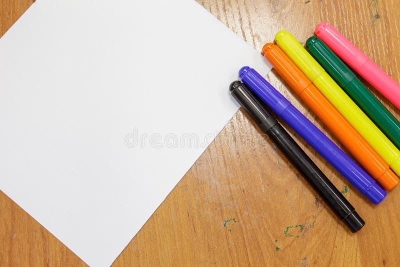 Ένα σύνολο έγχρωμων δεικτών και ένα φύλλο λευκού χαρτιού στο τραπέζι στοκ φωτογραφία με δικαίωμα ελεύθερης χρήσης