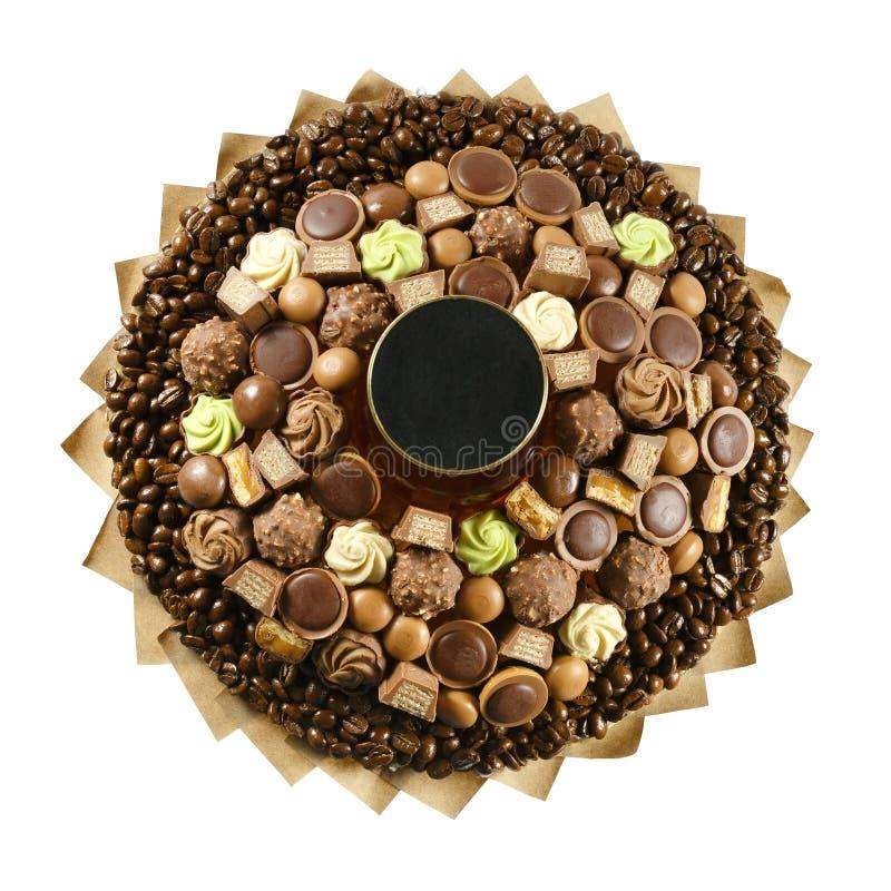 Ένα σύνολο εύγευστων καραμελών σοκολάτας, που πλαισιώνεται με τα φασόλια καφέ σε ένα άσπρο υπόβαθρο στοκ εικόνα