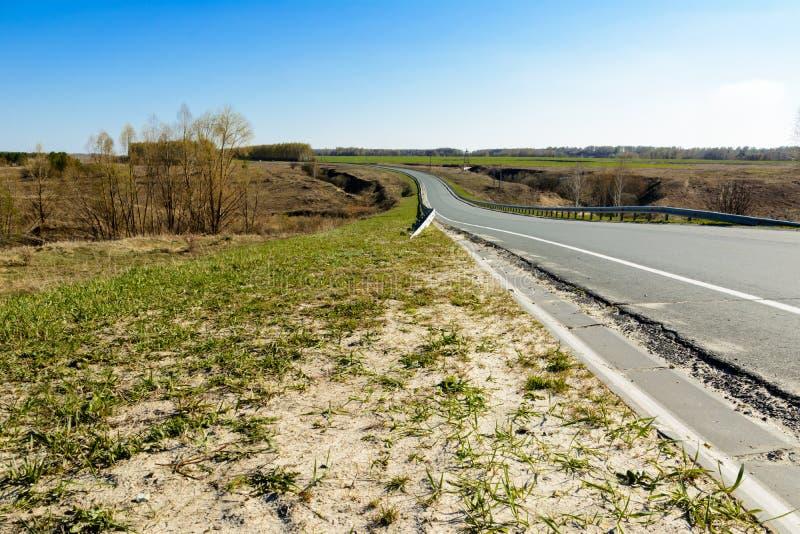 Ένα τέντωμα εθνικών οδών τυλίγματος στην απόσταση ενάντια στο σκηνικό ενός όμορφου τοπίου άνοιξη, τομείς, λιβάδια, δάση και στοκ εικόνες