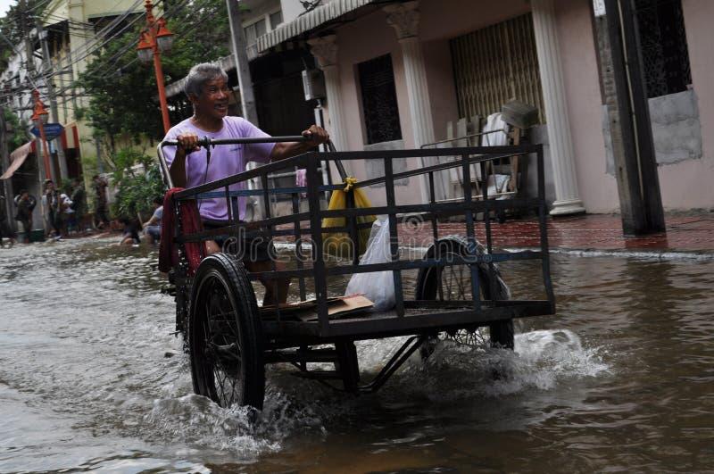 Ένα ταϊλανδικό άτομο γελά όπως οδηγεί κοντά σε μια πλημμυρισμένη οδό της Μπανγκόκ, Ταϊλάνδη, στις 30 Νοεμβρίου 2011 στοκ φωτογραφία