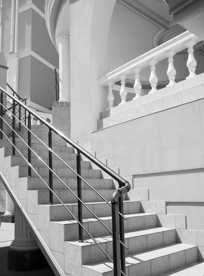 Ένα τεμάχιο μιας σκάλας με τα σύγχρονα κιγκλιδώματα που οδηγούν σε ένα κτήριο με τις στήλες και τα εκλεκτής ποιότητας κιγκλιδώματ στοκ φωτογραφίες