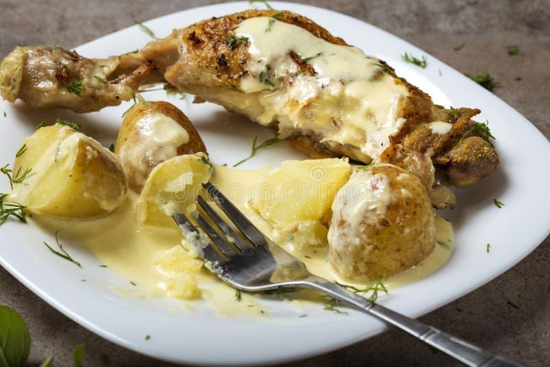 Ένα τηγανισμένο πόδι κοτόπουλου με τις καινούριες πατάτες και την ξινή σάλτσα κρέμας στοκ εικόνα με δικαίωμα ελεύθερης χρήσης