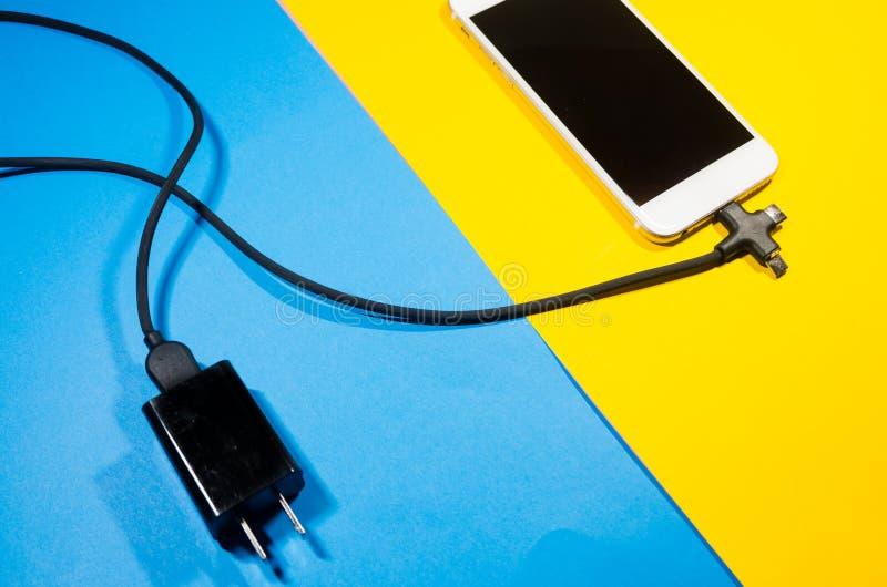 Ένα τηλέφωνο χρέωσης σύνδεσε με το φραγμό προσαρμοστών μέσω του μαύρου καλωδίου στοκ φωτογραφία