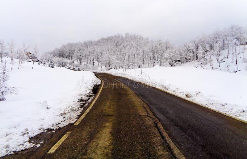 Ένα τοπίο βουνών με το χιόνι και την οδό στοκ φωτογραφία με δικαίωμα ελεύθερης χρήσης