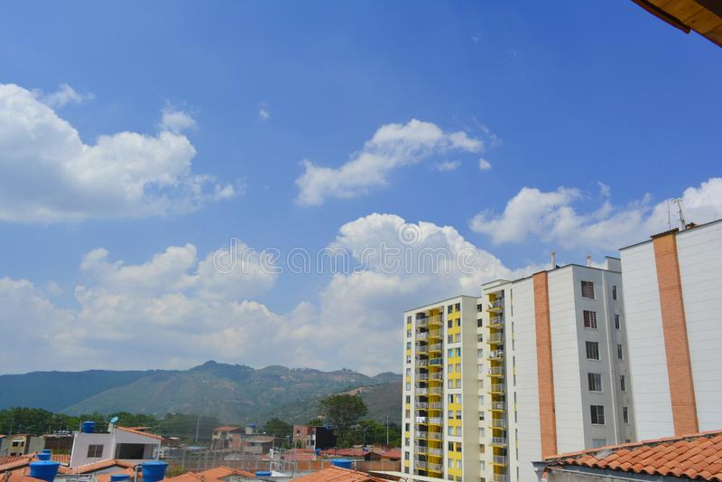 Ένα τοπίο μερικών σπιτιών που βλέπουν από τη στέγη και τον κίτρινο τοίχο οικοδόμησης με έναν μπλε ουρανό στο υπόβαθρο στοκ εικόνες