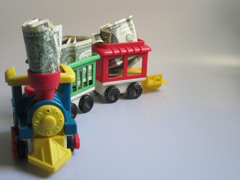 Ένα τραίνο τρέχει σε ένα άσπρο σύνολο υποβάθρου των χρημάτων στοκ φωτογραφίες με δικαίωμα ελεύθερης χρήσης
