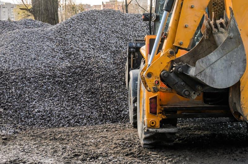 Ένα τρακτέρ με έναν κάδο φορτώνει το αμμοχάλικο πετρών σε ένα εργοτάξιο οικοδομής στοκ φωτογραφίες με δικαίωμα ελεύθερης χρήσης