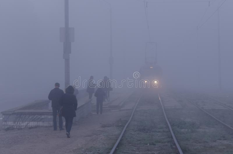 Ένα τραμ με τα φω'τα ομίχλης πηγαίνει σε μια στάση δημόσιων συγκοινωνιών στοκ φωτογραφίες