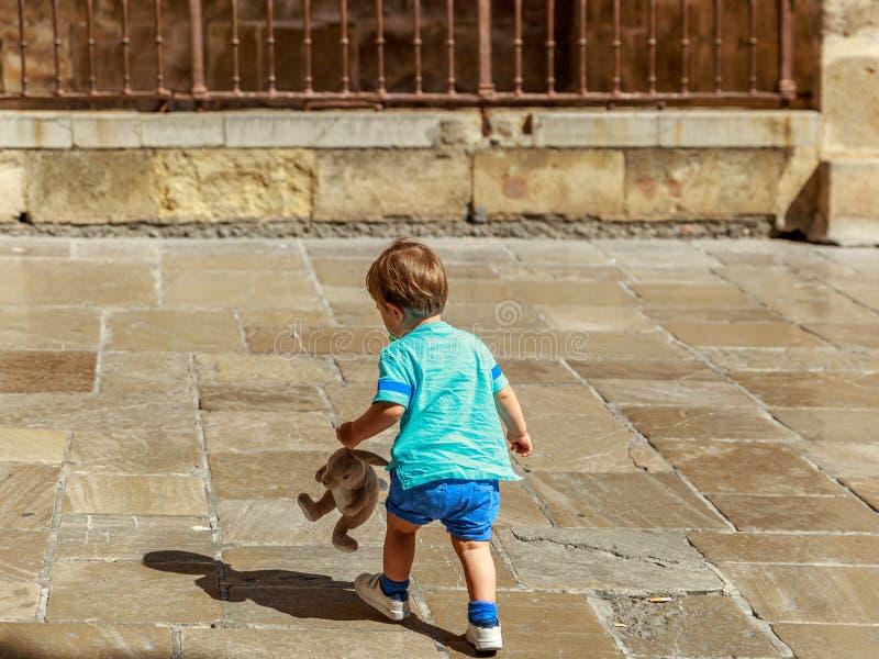 Ένα τρυφερό παιδί περπατά με την κούκλα του σε μια οδό στοκ εικόνες με δικαίωμα ελεύθερης χρήσης