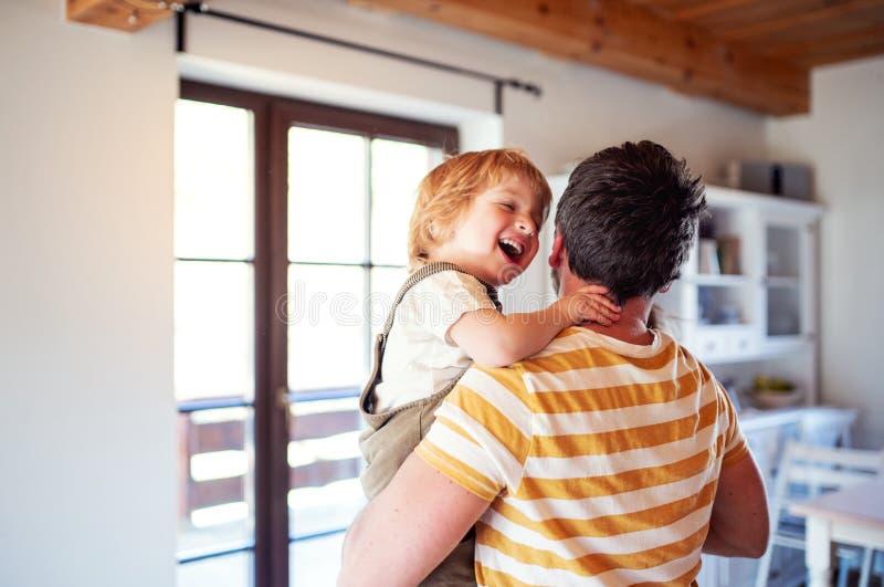 Ένα φέρνοντας αγόρι μικρών παιδιών πατέρων στο εσωτερικό στο σπίτι, γέλιο στοκ εικόνες με δικαίωμα ελεύθερης χρήσης