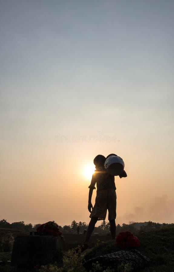 Ένα φέρνοντας δοχείο νερού προσώπων στο χρόνο ηλιοβασιλέματος, U Mrauk, το Μιανμάρ στοκ εικόνα