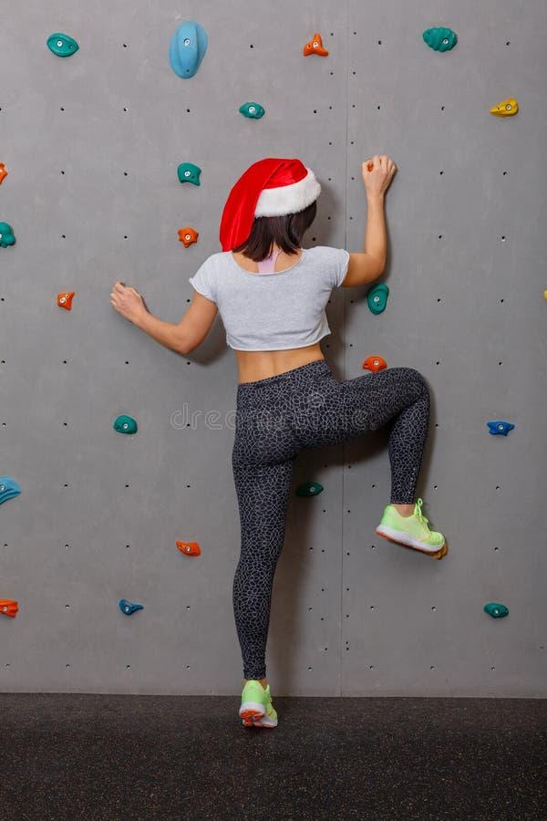 Ένα φίλαθλο κορίτσι είναι σε ένα κόκκινο καπέλο Χριστουγέννων, αναρριχείται επάνω στους τοίχους για την αναρρίχηση βράχου στοκ εικόνα