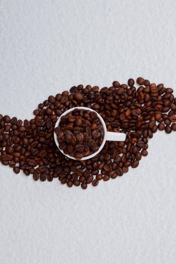 Ένα φλιτζάνι καφέ γεμάτο φασόλια στέκεται πάνω σε ένα σωρό καφέ στοκ εικόνες