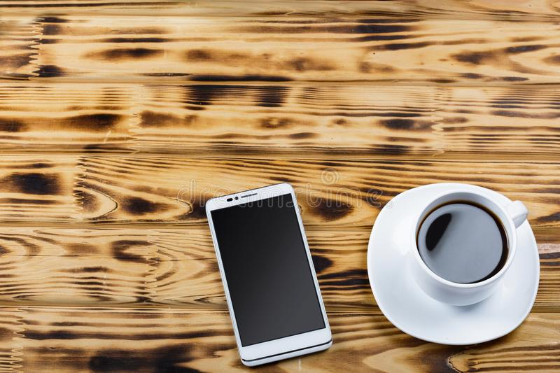 Ένα φλιτζάνι του καφέ και ένα άσπρο smartphone σε ένα ξύλινο γραφείο γραφείων ή σε έναν πίνακα σε έναν καφέ στοκ εικόνες