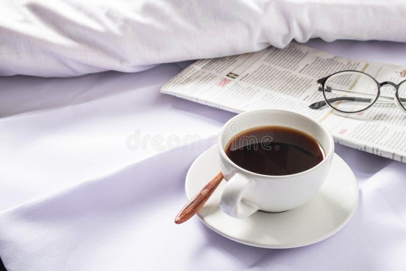 Ένα φλιτζάνι του καφέ και μια εφημερίδα σε ένα άσπρο κρεβάτι το πρωί στοκ εικόνες