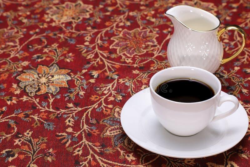 ένα φλιτζάνι του καφέ και μια κανάτα γάλακτος στοκ φωτογραφία με δικαίωμα ελεύθερης χρήσης