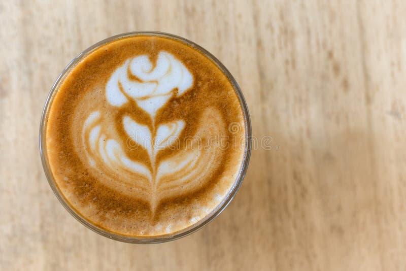 Ένα φλιτζάνι του καφέ με την τέχνη latte αυξήθηκε σχέδιο λουλουδιών σε ένα άσπρο φλυτζάνι καφέ στον ξύλινο πίνακα στη καφετερία στοκ φωτογραφίες