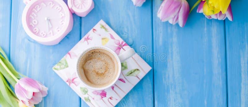 Ένα φλιτζάνι του καφέ σε ένα μπλε ξύλινο υπόβαθρο Φωτεινά χρώματα Ανθοδέσμη των λουλουδιών κίτρινων και ρόδινων Το ρόδινο ρολόι ε στοκ εικόνες