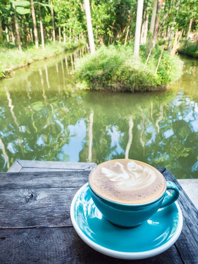 Ένα φλιτζάνι του καφέ στον ξύλινο πίνακα στοκ φωτογραφία με δικαίωμα ελεύθερης χρήσης