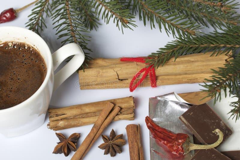 Ένα φλιτζάνι του καφέ στον πίνακα και τη σοκολάτα Ραβδιά κανέλας και λοβοί του κόκκινου πιπεριού δίπλα στους κλάδους έλατου Σε μι στοκ φωτογραφία με δικαίωμα ελεύθερης χρήσης