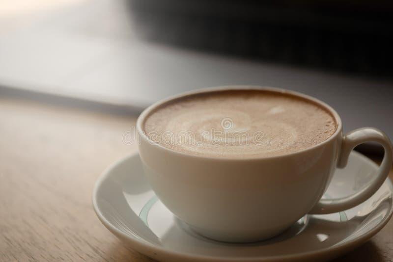 Ένα φλιτζάνι του καφέ στο γραφείο, φλιτζάνι του καφέ υπό εξέταση, κούπα του καφέ latte, κλείνει επάνω την έννοια στοκ εικόνες