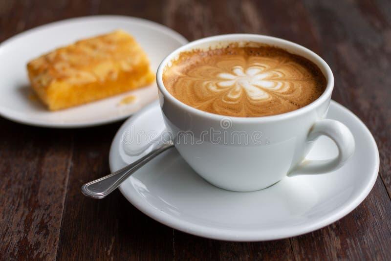 Ένα φλιτζάνι του καφέ latte στον ξύλινο πίνακα με το επιδόρπιο στοκ φωτογραφία