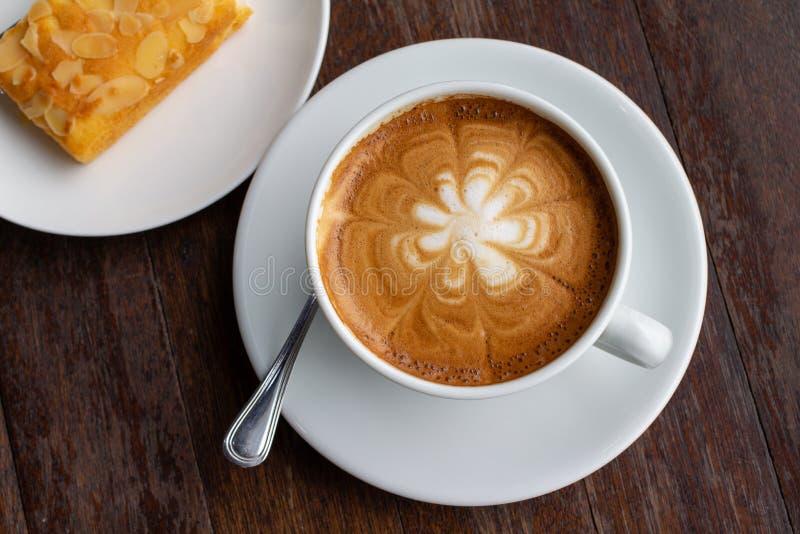 Ένα φλιτζάνι του καφέ latte στον ξύλινο πίνακα με το επιδόρπιο στοκ εικόνα