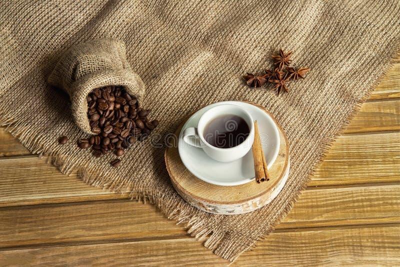Ένα φλυτζάνι καφέ με την κανέλα και badyan σε ένα πιατάκι και φασόλια καφέ σε έναν σάκο σε έναν ξύλινο πίνακα στοκ φωτογραφίες