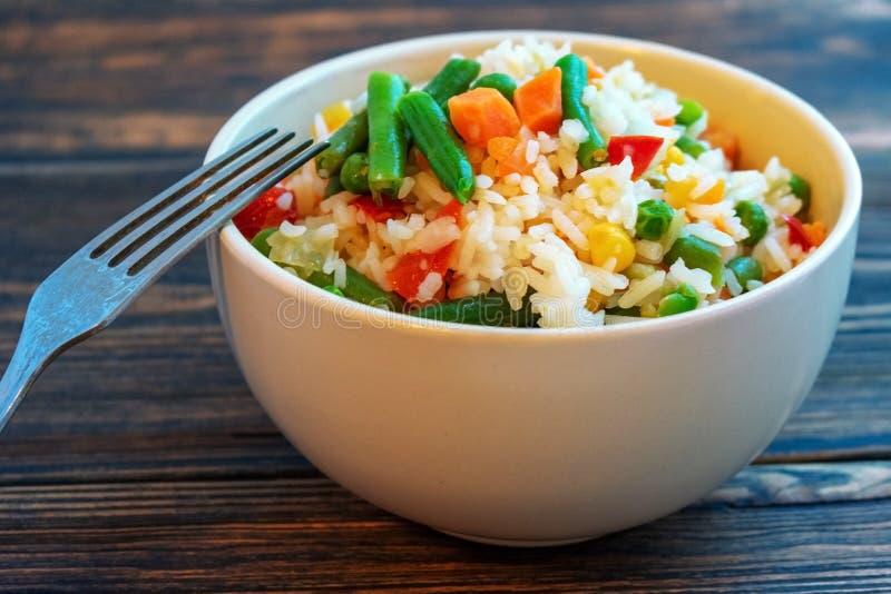 Ένα φλυτζάνι του άσπρου ρυζιού με τα λαχανικά σε ένα σκοτεινό ξύλινο υπόβαθρο Προετοιμασμένος χωρίς απώλεια βιταμινών στοκ εικόνες με δικαίωμα ελεύθερης χρήσης