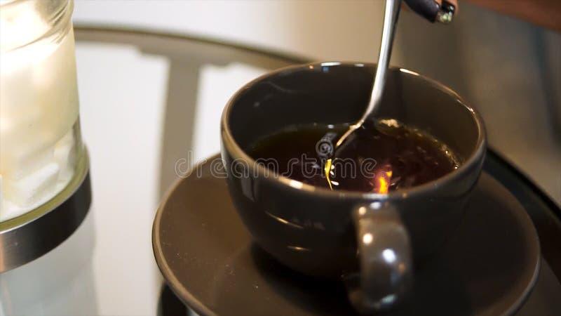 Ένα φλυτζάνι του ανακατώματος του τσαγιού Ανακάτωμα του τσαγιού με το κουτάλι σε σε αργή κίνηση Ανακατώστε το γλυκό φλυτζάνι τσαγ στοκ εικόνες
