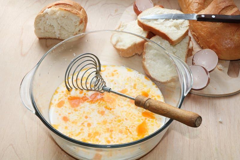Ένα φλυτζάνι του γάλακτος με τα αυγά και κομμάτια του άσπρου ψωμιού, η διαδικασία τις τηγανισμένες φρυγανιές στοκ φωτογραφίες