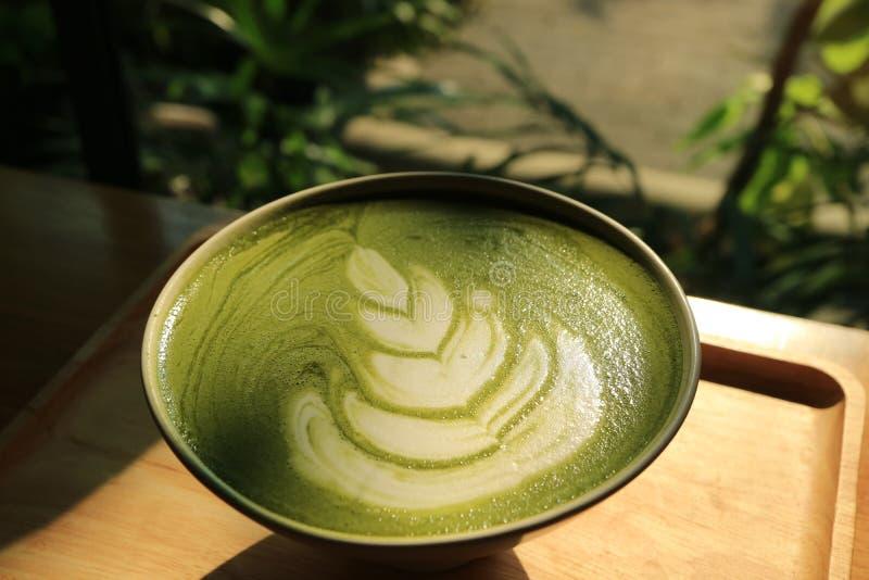 Ένα φλυτζάνι του καυτού ιαπωνικού πράσινου τσαγιού Latte Matcha στο φως του ήλιου στοκ εικόνα