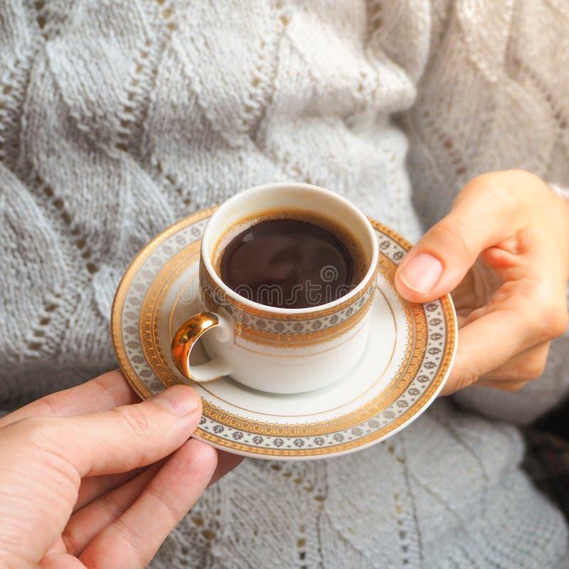 Ένα φλυτζάνι του μαύρου καφέ στα χέρια της κινηματογράφησης σε πρώτο πλάνο στοκ φωτογραφίες