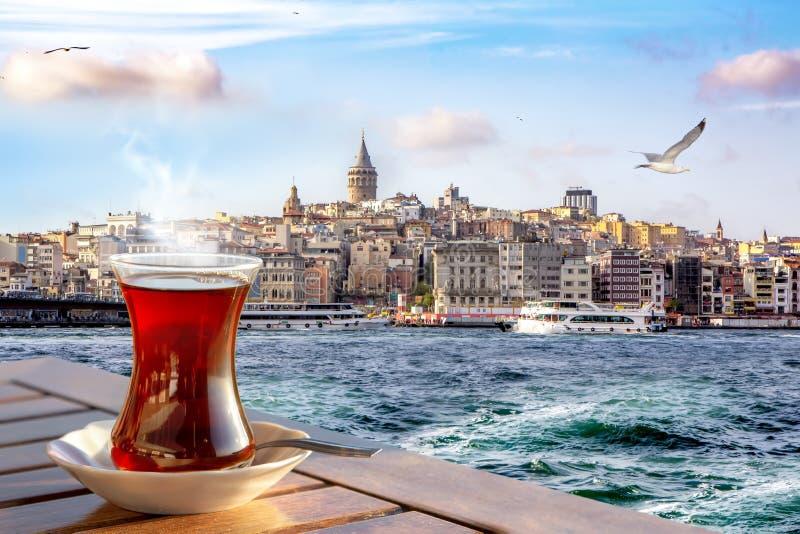 Ένα φλυτζάνι του τουρκικού τσαγιού σε ένα παραδοσιακό γυαλί στα πλαίσια του χρυσού κέρατου και του πύργου Galata στη Ιστανμπούλ στοκ φωτογραφία με δικαίωμα ελεύθερης χρήσης